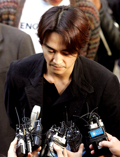 Song Seung-heon, in his exam gown, waits his turn before the examination table.