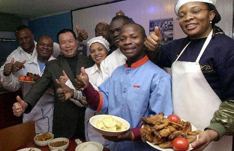 Emmanuel (second from right), the owner of a Nigerian restaurant, poses with his wife (right), staff and building owner at his restaurant in Itaewon, Seoul.