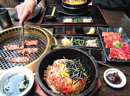 A menu with kalbi (roast beef ribs) and bibimbap (boiled rice with assorted mixtures) served by Japanese restaurant Gyu-Kaku in Manhattan.