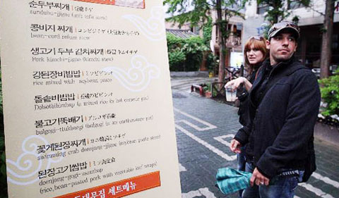 Foreigners pass by a menu board of a Korean restaurant in Insa-dong, Seoul.