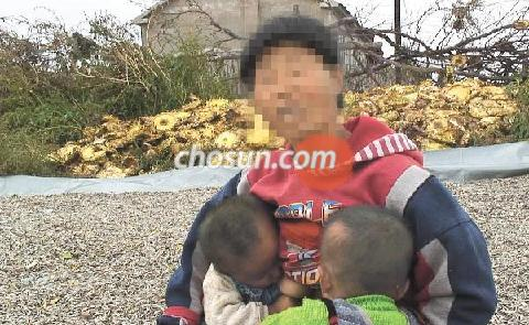 Cho Kyung-sook breastfeeds her three-year-old twins borne of her Chinese husband.