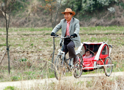 Former President Roh Moo-hyun rides a rickshaw with his granddaughters in the carriage at Bongha Village in April 2008. /Official website for the late former President Roh Moo-hyun
