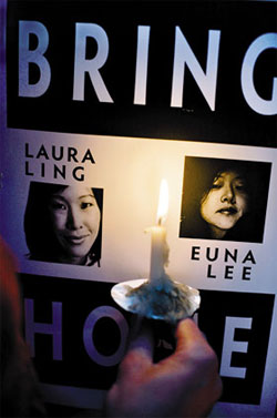 A sign is lit by a candle at a vigil for Laura Ling and Euna Lee, two American journalists who went on trial in North Korea on Thursday, at the Wokcano Cafe in Santa Monica, California on Wednesday. /AP