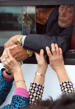 North Koreans reach out of a bus window to grab the hands of South Korean family members before leaving the family reunion center in Mt. Kumgang on Oct. 1. /Yonhap
