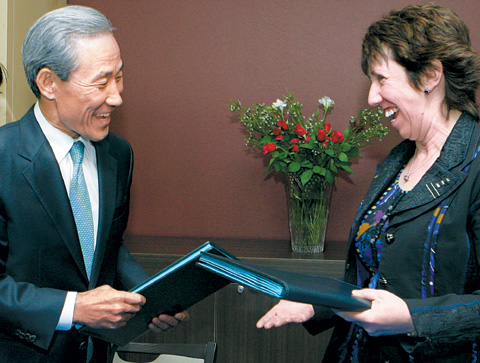 Trade Minister Kim Jong-hoon (left) and EU Trade Commissioner Catherine Ashton exchange the initialed Korea-EU FTA in Brussels on Thursday. /AP-Newsis