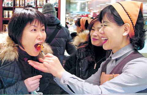 A Japanese tourist tastes kimchi at a department store in Seoul.