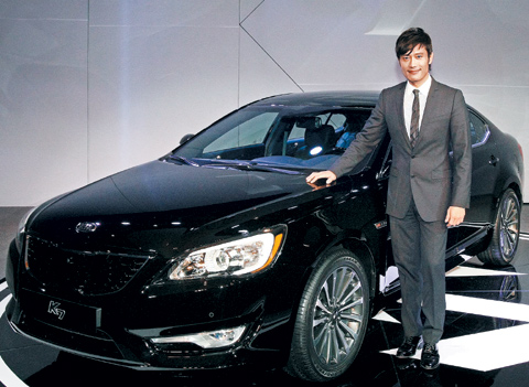 Actor Lee Byung-hun poses in front of Kias K7 luxury sedan at an event to showcase the new vehicle at a hotel in Seoul on Oct. 24. /Courtesy of Kia Motors