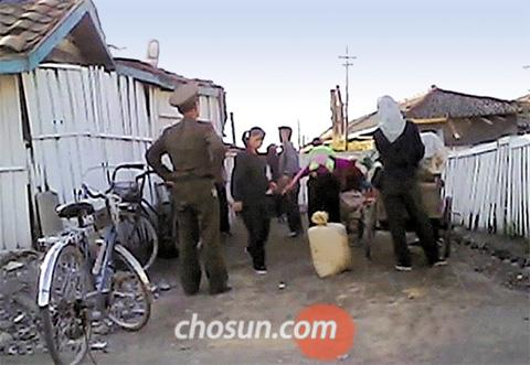 A peoples security officer cracks down on illegal peddlers near the Onsong market in North Hamgyong Province, North Korea in October last year.