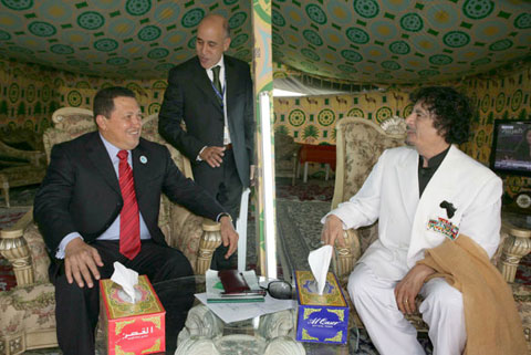 Libyan head of state Muammar al-Qaddafi (right) talks to Venezuelan President Hugo Chavez (left) in his Bedouin-style tent during the Arab-Latin American Summit in Doha, Qatar in March 2009. /EPA