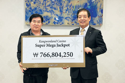 Jackpot winner Ahn Seung-pil (left) poses with a Kangwon Land staffer after singing an agreement to donate the prize money to KAIST at the casino on Monday. /Courtesy of Kangwon Land