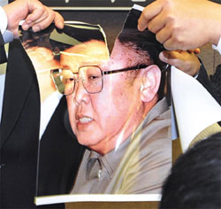 Activists tear apart the photo of North Korean leader Kim Jong-il at the Press Center in Seoul on Monday. /Newsis