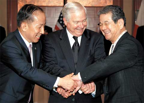 The defense ministers of Korea, China and the U.S. hold hands at the Ninth Asia Security Conference in Singapore on Saturday. From left, Koreas Kim Tae-young, the U.S. Robert Gates and Japans Toshimi Kitazawa /AP-Yonhap