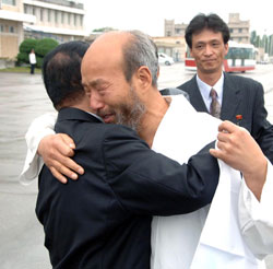 The Rev. Han Sang-ryeol (center) hugs a North Korean official on arrival at Sunan Airport in Pyongyang on Saturday. /[North] Korean Central News Agency-Yonhap