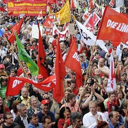 Demonstrators carry banners and flags to protest the governments planned austerity measures in Stuttgart, Germany on June 12, 2010. /AP