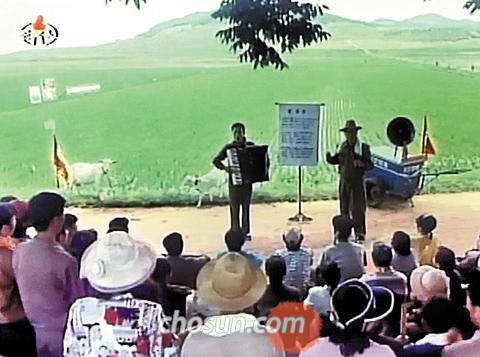 A screen grab from a North Korean film released early this year shows a man teaching villagers the song