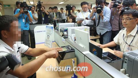 An officer photographs and fingerprints a foreigner entering Korea at Incheon International Airport on Monday.