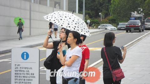 Chinese tourists take a photo near the main gate of Ewha Womans University in Seoul on Sept. 11. 