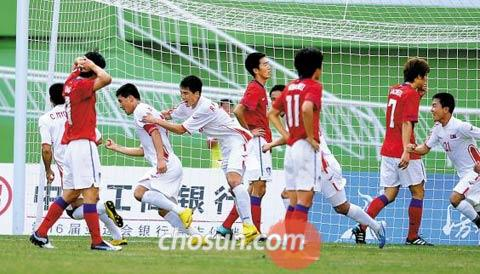 North Korean footballers (in white) celebrate after scoring a goal in the Group C opening match against South Korea at Yuexiushan Stadium at the Guangzhou Asian Games on Monday.