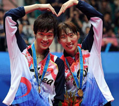 Shin Baek-cheol (left) and Lee Hyo-jung make a heart shape after winning a gold medal in mixed doubles badminton at the 2010 Asian Games in Guangzhou on Sunday.