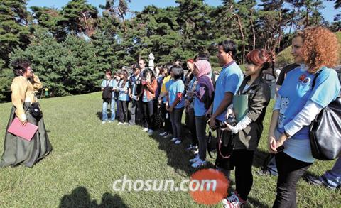 Visitors listen to a guide speaking about the history of Hongneung, the tomb of King Gojong of the Chosun Dynasty, in Namyangju, Gyeonggi Province. 