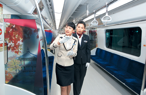 Crew check the interior of the airport train operating between Seoul Station and Incheon International Airport at the opening ceremony in the railway station on Tuesday. /Yonhap