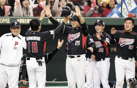 Playboys captain Kim Seung-woo celebrates with his teammates after making a run during a friendly match against a team of retired Japanese professional baseball players on Sunday. /Courtesy of Sports Nippon