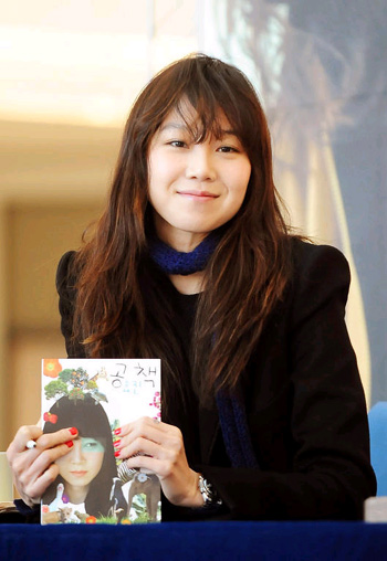 Actress Kong Hyo-jin autographs her book on the environment in Seoul on Sunday. /Newsis