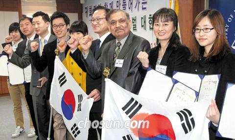 Justice Minister Lee Kwi-nam (fourth from right) and naturalized Koreans including Roy Alok Kumar from India (third from right) smile at a ceremony to award them certificates of naturalization at the Government Complex in Gwacheon, Gyeonggi Province on Monday.