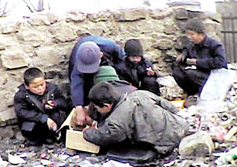 A group of boys, presumably beggars, eat what they have collected from heaps of waste at a railway station in South Pyongan Province, North Korea in this grab from an undated video clip obtained from a defector by Grand National Party lawmaker Chung Ok-nim.