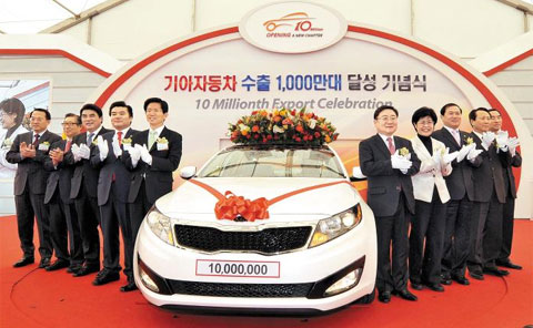 Kia Motors vice chairman Lee Hyoung-keun (sixth from left) and Gyeonggi Province Governor Kim Moon-soo (fifth from left) applaud at an event to mark the automaker's 10 millionth exported car at Pyeongtaek Port on Thursday. /Courtesy of Kia Motors