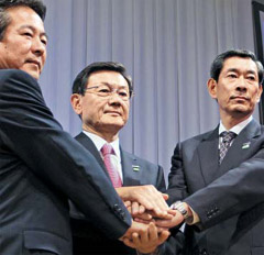 Panasonic chairman Fumio Ohtsubo (center) links hands with Sanyo chairman Seiichiro Sano (left) and Panasonic Electric Works chairman Shusaku Nagae after announcing a plan to acquire Sanyo in July last year. /Bloomberg