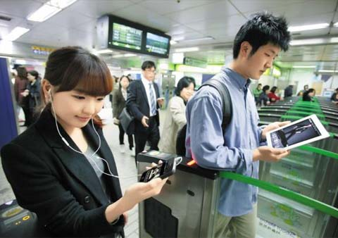 Commuters use a smartphone and tablet PC as they pass through subway turnstiles. /Courtesy of KT