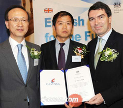 A North Korean defector poses with U.K. Ambassador Martin Uden (right) and Unification Minister Hyun In-taek (left) at the British Council in Seoul on Tuesday after winning a scholarship.
