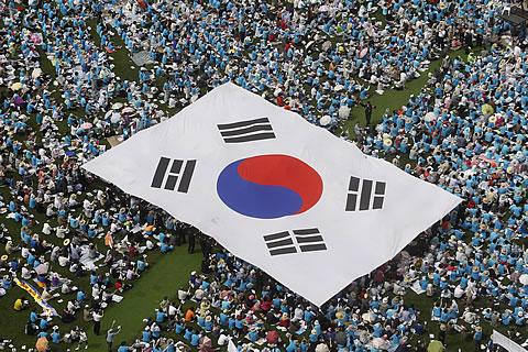 People carry a large scale South Korean national flag during an anti-North Korea rally marking Memorial Day in Seoul, on June 6, 2011. /Reuters