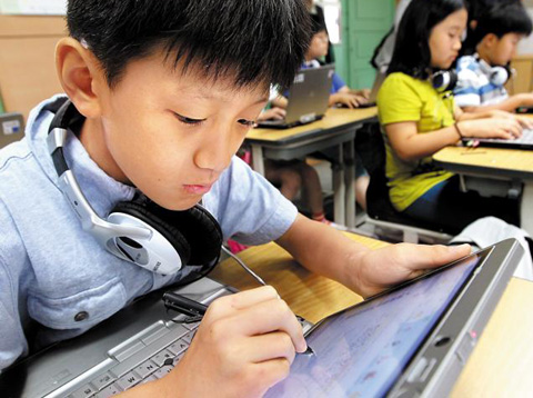 Students read textbooks on laptop PCs at Guil Elementary School in Seoul on Wednesday. /Yonhap