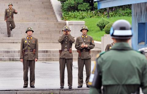 North Korean soldiers look toward the south as a South Korean soldier (right) stands guard in the demilitarized zone separating the two Koreas on July 15, 2011. /Reuters