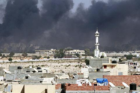 Smoke rises above downtown Tripoli following fighting at Bab al-Aziziya compound on Aug. 23, 2011. /Reuters