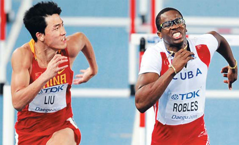 Liu Xiang of China (left) looks at Cubas Dayron Robles in the mens 110-m hurdle final at the IAAF World Athletics Championships on Monday. /Newsis