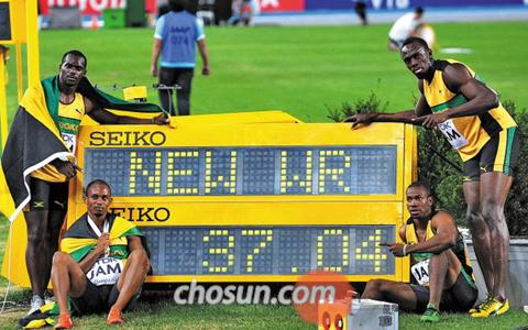 Jamaican athletes pose by a billboard after winning the mens 400-m relay in a new world record of 37.04 seconds in the IAAF World Athletics Championships in Daegu on Sunday.