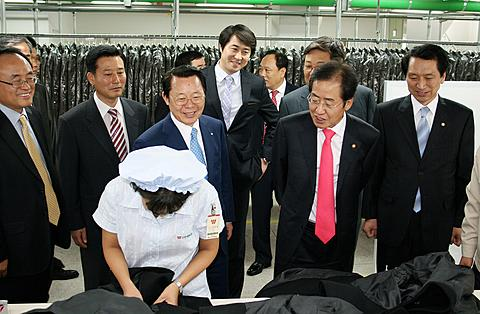 South Koreas ruling Grand National Party chief Hong Joon-pyo, second from right, looks at a North Korean worker during his visit to a factory in the inter-Korean industrial park in Kaesong, North Korea on Sept. 30, 2011.