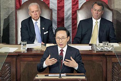 President Lee Myung-bak speaks to a joint meeting of Congress as Vice President Joe Biden (left) left, and Speaker of the House John Boehner (right) look on at the Capitol in Washington on Oct. 13, 2011. /AP