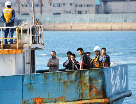 Japan Coast Guard personnel, in white helmets, keep watch over Chinese fishermen on the stern of their fishing boat that was brought to Nagasaki Harbor in Nagasaki, southwestern Japan, by the coast guard on Monday. /AP-Newsis
