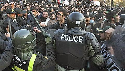 Iranian police officers prevent some protesters from entering the British Embassy, in Tehran, Iran, on Nov. 29, 2011. /AP