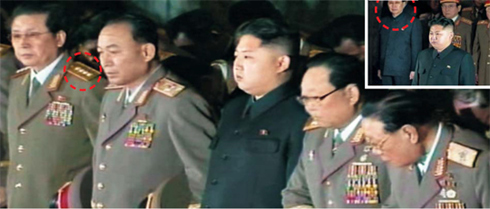 Jang Song-taek (left), the uncle of new North Korean leader Kim Jong-un (center) with four-star insignia on his epaulettes, pays his respects to the body of North Korean leader Kim Jong-il in a photo released Sunday by the North Korean Central TV. In the photo (insert) released last Tuesday, he wears a Mao suit like Kim Jong-un. /[North] Korean Central TV