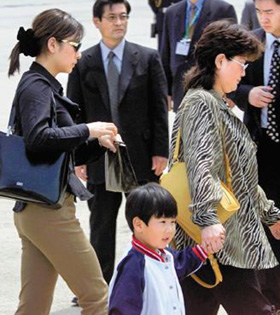 From right, former North Korean leader Kim Jong-ils eldest son Kim Jong-nams wife, his eldest son and his secretary walk out of Narita Airport in Japan on May 4, 2001, when Kim was caught with a forged passport. /Mainichi Shimbun