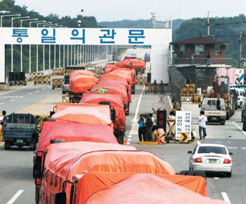 Trucks loaded with rice cross the inter-Korean checkpoint to Kaesong on July 26, 2006 (file photo).