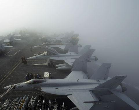 U.S. Navy F/A-18F Super Hornet fighter jets sit in heavy fog on the deck of the USS George Washington, during a joint military exercise off South Koreas West Sea (file photo). /AP