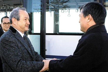 Naguib Sawiris (left), executive chairman of Orascom Telecom, holds hands with a North Korean official during his visit to Pyongyang on Wednesday. /[North] Korean Central News Agency-Yonhap