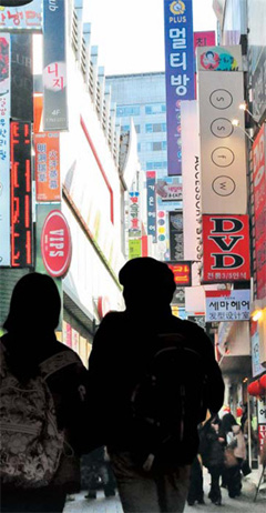 Students walk down a street in Myeong-dong clustered with private rooms where users sing karaoke or play video games.