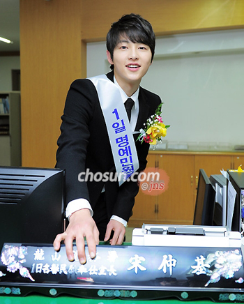 Song Joong-ki shows off his nameplate at the Yongsan District Tax Office on Tuesday.